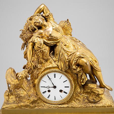 A mid 19th century brass and gilt brass mantel clock.
