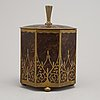 An art nouveau brass and burr walnut tobacco jar and cover from around year 1900.