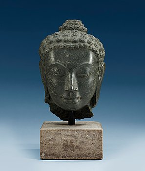 A stone head of Buddha. Thailand. Height incl stand 32,5 cm.