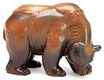 A Gunnar Nylund stoneware figure of a bear, Rörstrand. Height 17 cm, length 23 cm.