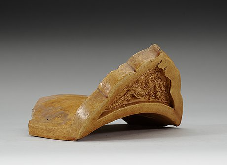 A yellow glazed end-tile, with dragon in relief, ming dynasty (1368-1644).