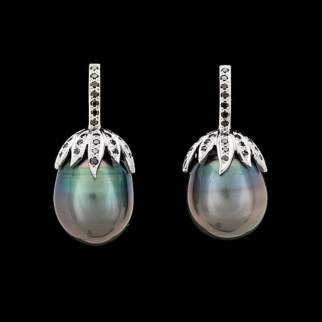 A pair of cultured tahiti pearl, app. 16 mm, and black diamond earrings.