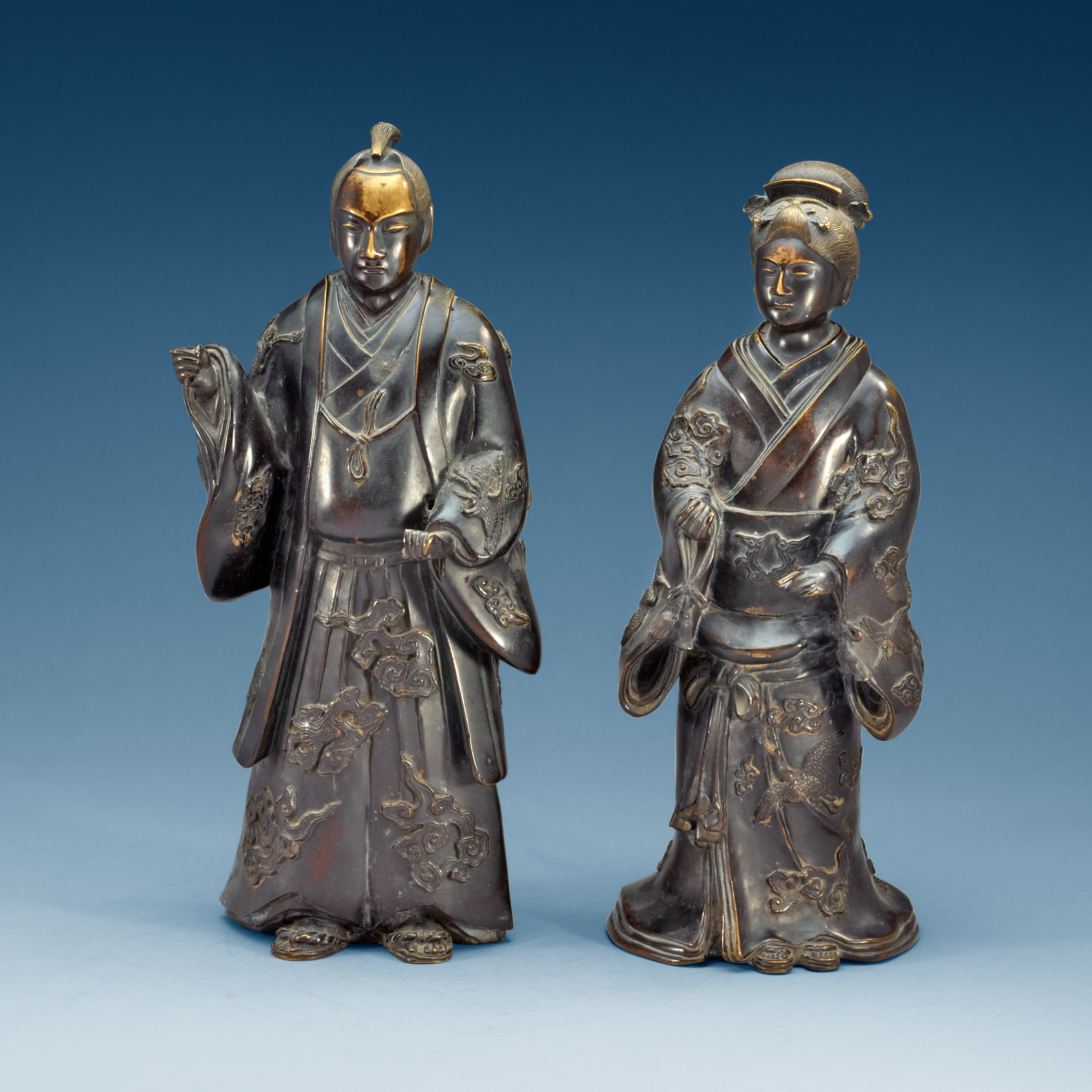 two standing japanese bronze sculptures of a samurai and elegant