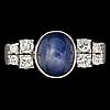 Ring, cabochonslipad blå safir med briljantslipade diamanter, tot. ca 0.45 ct.