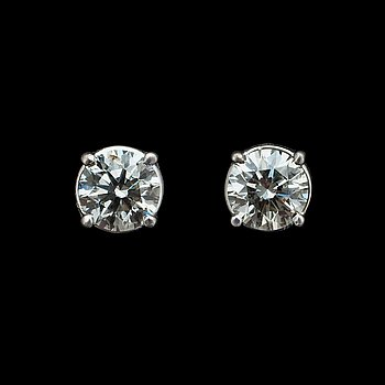 1057. A pair of brilliant cut diamond ear studs.