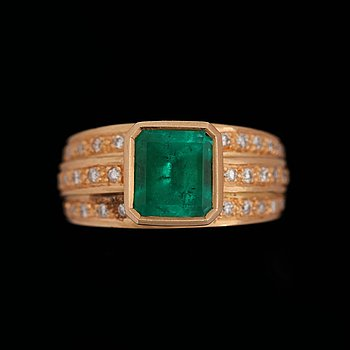 A step cut emerald ring set with brilliant cut diamonds.
