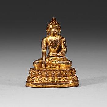 213. A gilt Tibetan bronze figure of Buddha, 16th Century or older.