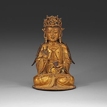 210. A gilt-bronze figure of a seated Guanyin, Ming dynasty (1368-1644).