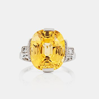 1111. A circa 13.50 ct fancy yellow sapphire and brilliant-cut diamond ring. Total carat weight of diamonds circa 0.10 ct.