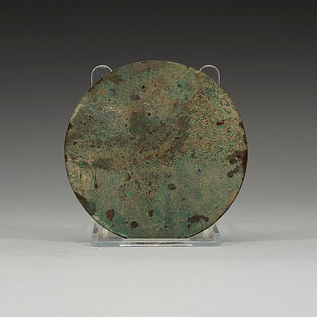 A bronze mirror decorated with a highly stylized dragon-pattern, han dynasty (206 bc - ad 220).