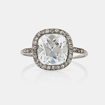 1105. RING med en äldre kuddslipad diamant ca 3.50 ct med omgivande krans av mindre diamanter, troligen tillverkad av Cartier.