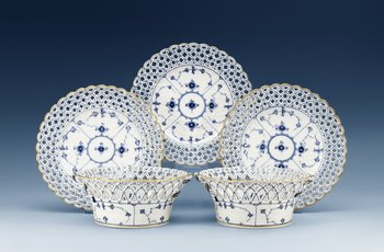A set of 12 Royal Copenhagen 'Musselmaalet' dessert dishes and a pair of chestnut baskets, Denmark, 19th Century. (14). Diameter of dishes, 23,5 cm, length of baskets 20 cm.