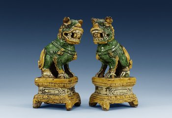 A pair of green and yellow glazed dogs, late Ming dynasty (1368-1644). (2). Height 24 cm.