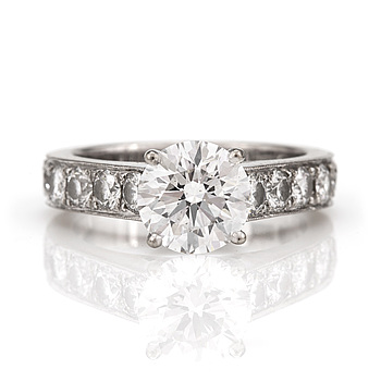 A ring set with round, brilliant-cut diamonds, the central diamond 1,76 ct, quality E/SI1 (according to GIA certificate.