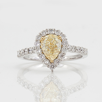 A ring with a Fancy Yellow diamond ca 1.06ct and 20 brilliant total carat weight circa 1.49cts. Quality circa G-H/VS-SI.