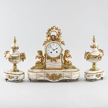 A table clock and two decoratives urn, around year 1900.