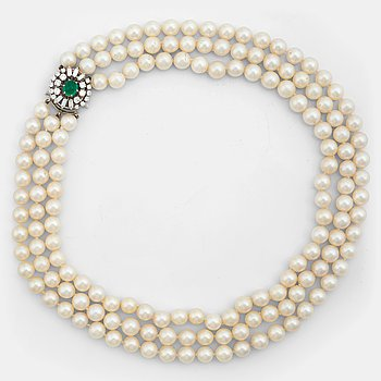 791. A three strand cultured pearl necklace, clasp with cabochon cut emerald circa 1.68 cts and diamonds.
