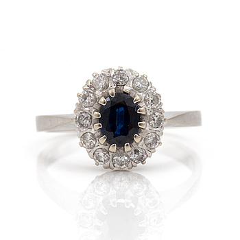 A ring set with an oval, mixed-cut sapphire surrounded by round brilliant-cut diamonds.