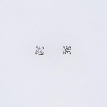A pair of brilliant cut diamond earrings.