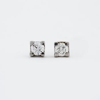 A apir of brilliant cut diamond earrings.