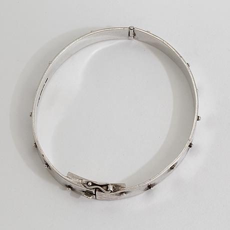 A bracelet marked aek 916h, helsingfors, 1966.