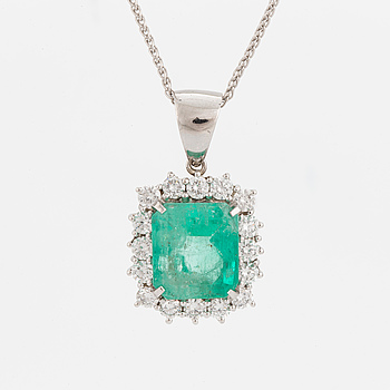 An 18K white gold chain and a pendant set with an emerald-cut emerald and round, brilliant-cut diamonds.