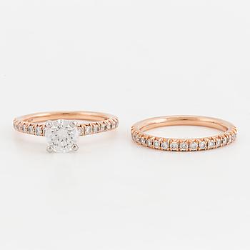 RINGAR, två stycken, med briljantslipade diamanter. Den större diamanten 0,77 ct enligt certifikat.