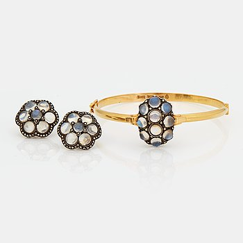 772. A BANGLE and a PAIR OF EARRINGS set with cabochon-cut moonstones and marcasites.