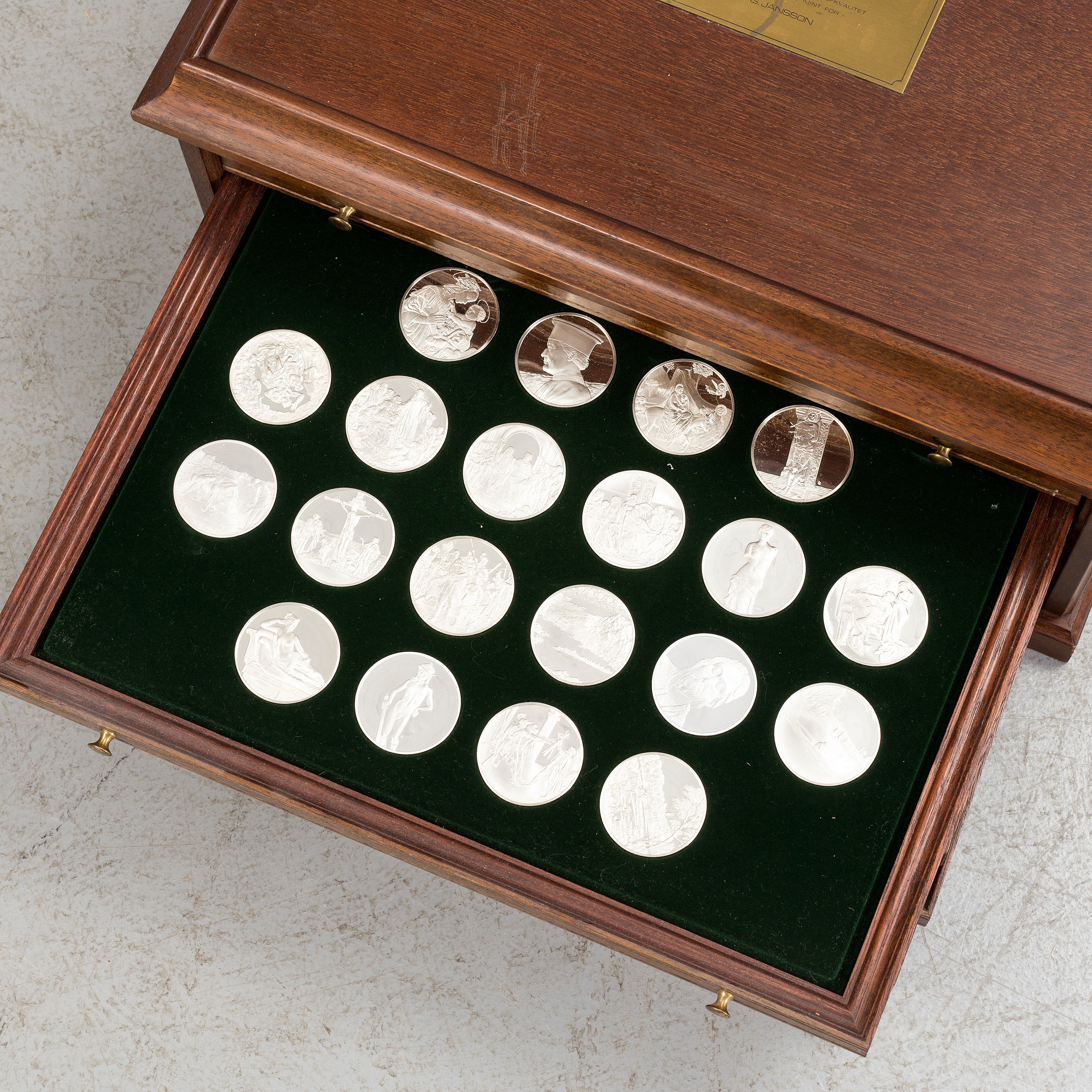 100 sterling silver coins in a wooden cabinet by Franklin mint