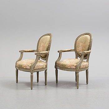 a pair of Louis XVI-style armchairs from the 20th century.