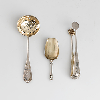 A Russian parcel-gilt tea caddy spoon, sugar thongs and sugar sifter, maker's mark Grigory Spitnev, Moscow, 1898-1914.